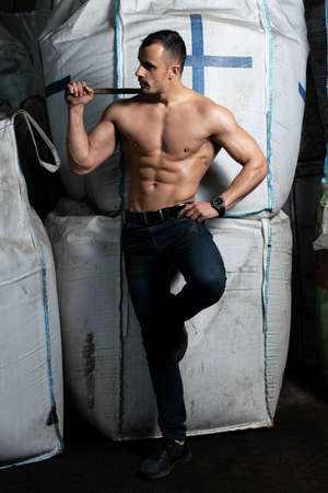 Young Man Standing Strong in Warehouse With Big Bags and Flexing Muscles - Muscular Athletic Bodybuilder Fitness Model Posing