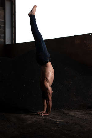 Handsome Man Keeping Balance on Hands in Warehouse - Muscular Athletic Bodybuilder Fitness Model Doing Handstand Push-up