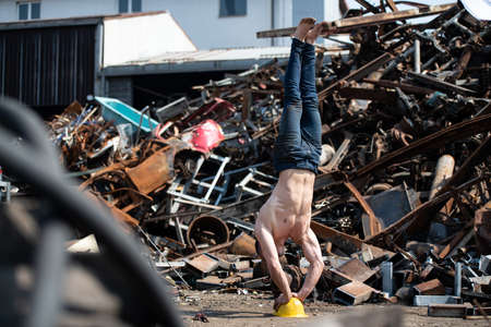 Handsome Man Keeping Balance on on Yellow Helmet With Hands in Old Industrial Junk Yard - Muscular Athletic Bodybuilder Fitness Model Doing Handstand Push-up