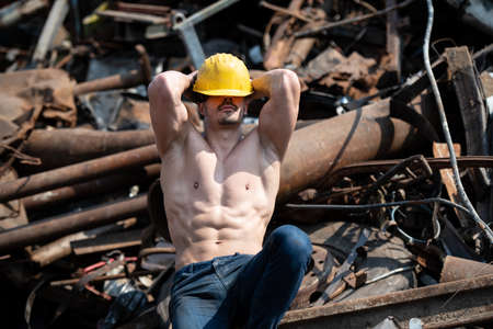 Handsome Man Sitting Strong in Scrap Metal Industrial Junkyard and Flexing Muscles - Muscular Athletic Bodybuilder Fitness Model Posing With Yellow Helmet