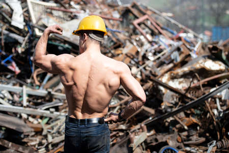 Portrait of a Young Physically Fit Man Standing in Industrial Junk Yard Showing His Well Trained Body With Yellow Helmet