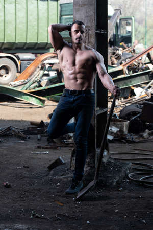 Portrait of a Young Physically Fit Man Standing With Shovel in Industrial Junk Yard Showing His Well Trained Body 免版税图像