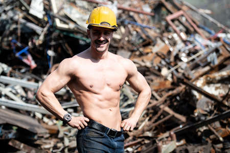 Young Man Standing Strong in Old Scrap Metal Garage and Flexing Muscles - Muscular Athletic Bodybuilder Fitness Model Posing With Yellow Helmet