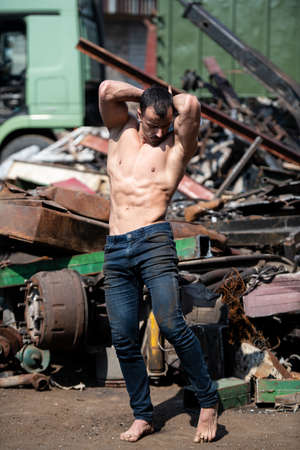 Portrait of a Young Physically Fit Man Standing in Industrial Junk Yard Showing His Well Trained Body 免版税图像