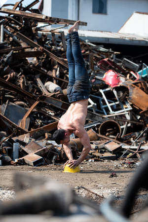 Young Man Keeping Balance on Yellow Helmet With Hands in Old Industrial Junk Yard - Muscular Athletic Bodybuilder Fitness Model Doing Handstand Push-up