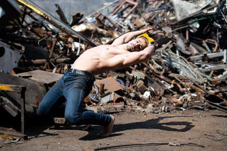 Young Man Keeping Balance on Hands in Old Industrial Junk Yard - Muscular Athletic Bodybuilder Fitness Model