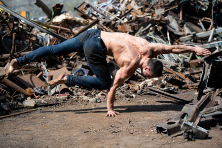 Young Man Keeping Balance on Hand in Old Industrial Junk Yard - Muscular Athletic Bodybuilder Fitness Model Doing Handstand Push-up