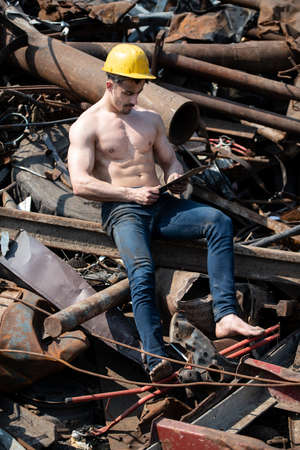 Portrait of a Young Physically Fit Man Sitting in Industrial Junk Yard Showing His Well Trained Body With Yellow Helmet