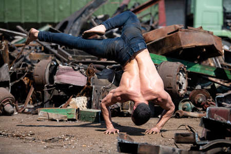 Young Man Keeping Balance on Hands in Old Industrial Junk Yard - Muscular Athletic Bodybuilder Fitness Model Doing Handstand Push-up