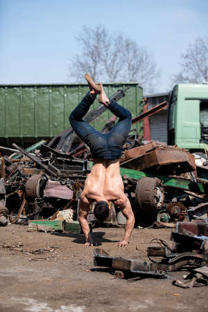Handsome Man Keeping Balance on Hands in Old Industrial Junk Yard - Muscular Athletic Bodybuilder Fitness Model Doing Handstand Push-up 免版税图像