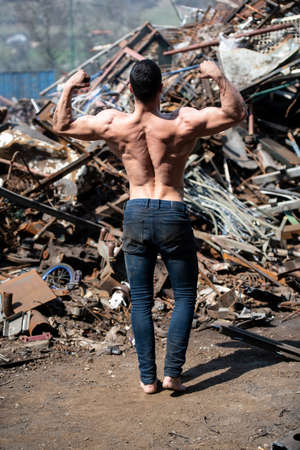 Young Man Standing Strong in Old Scrap Metal Garage and Flexing Muscles - Muscular Athletic Bodybuilder Fitness Model Posing 免版税图像