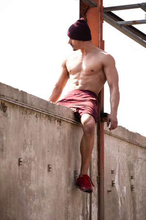 Resting Time - Confident Muscled Young Man Resting in Abandoned Warehouse After Exercising