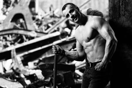 Young Man Standing Strong in Old Scrap Metal Garage and Flexing Muscles With Shovel - Muscular Athletic Bodybuilder Fitness Model Posing 免版税图像