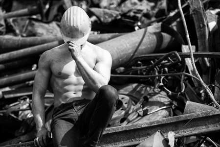 Young Man Sitting Strong in Old Scrap Metal Garage and Flexing Muscles - Muscular Athletic Bodybuilder Fitness Model Posing With Yellow Helmet 免版税图像