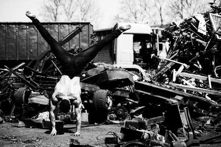 Handsome Man Keeping Balance on Hand in Old Industrial Junk Yard - Muscular Athletic Bodybuilder Fitness Model Doing Handstand Push-up