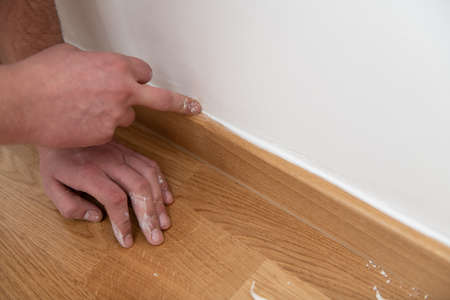 Construction Worker Use Finger Applying Silicone for Repairing and Installing Parquet in House Фото со стока