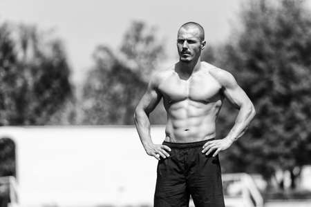Portrait Of A Young Physically Fit Man Showing His Well Trained Body Outdoor - Muscular Athletic Bodybuilder Fitness Model Posing After Exercises Standard-Bild