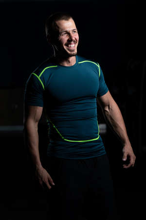 Portrait Of Handsome Personal Trainer Wearing Sportswear In Fitness Center Gym Standing Strong Foto de archivo