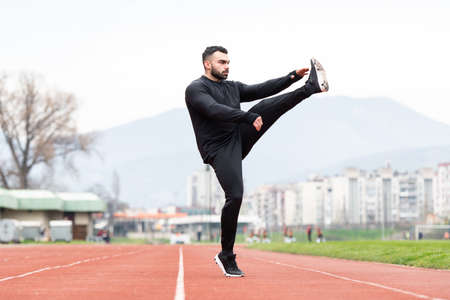 Sporty Man Stretching and Warming Up Legs for Running Fitness Workout on Track Exercising Outside