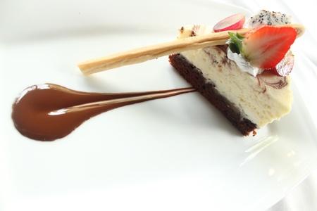 rebanada de pastel: Brownese tarta de queso de mármol y fresa para la decoración. Pedazo de la torta rebanada de postre.