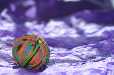A ball of elastic bands, of many different colors, placed on purple paper background.