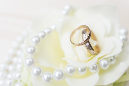 wedding rings on a flower with bright pearls Stock Photo