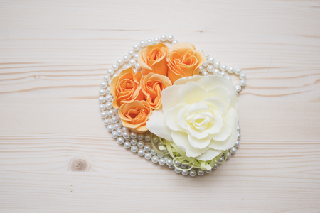 flowers and pearls composition on a wood background