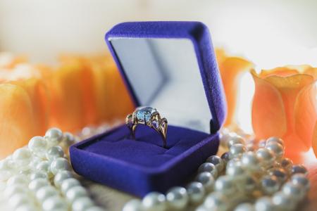 Goldring mit Topas in einer Geschenkbox auf Perlen Standard-Bild