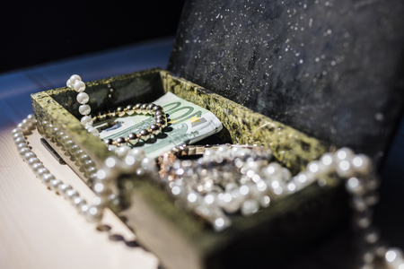 Pearl, gold bracelet and money in a box