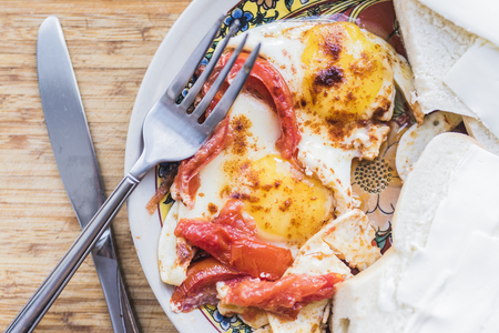 Fried eggs with tomato, sandwich, fork and knife