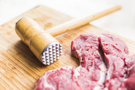 Fresh red meat and a hammer for beating meat Stock Photo