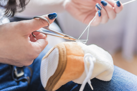 Womens hands cut off the thread after sewing Stock Photo