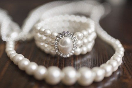 A bracelet made of white pearls with a large pearl and diamonds and a pearl necklace lie on a dark wooden background Stock Photo