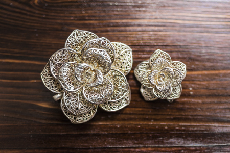 Large and small silver brooches in the form of a flower lie on a dark brown wooden background, top view.