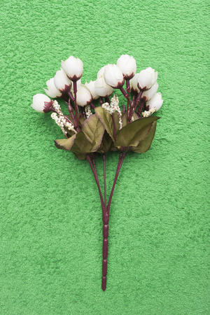 Artificial little white roses lie on an emerald green background