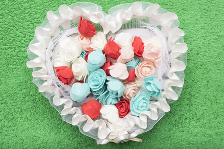 Artificial little white, red and turquoise roses lie in a white lace basket in the form of a heart on an emerald green background.