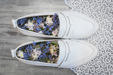 Womens white leather shoes with white and blue flowers inside and white lace on a light vintage background. Фото со стока