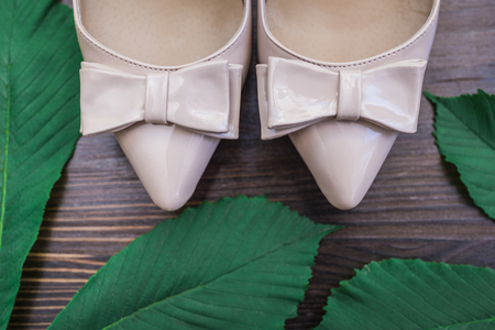 Beige lacquered shoes with a pointed nose and bow and bright green leaves on a dark wooden background.