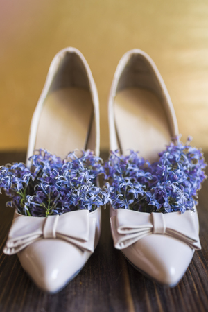 Womens beige lacquered high-heeled shoes with a sharp nose and bow and bright lilac flowers inside like a natural deodorant for shoes on a dark wooden and gold background.