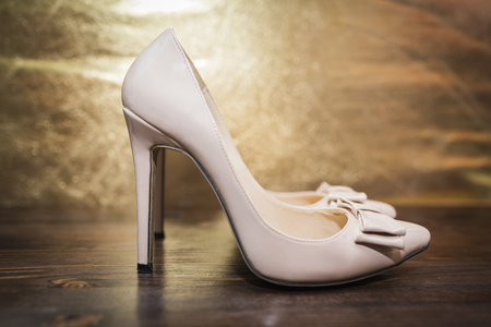 Womens beige lacquered shoes with a pointed nose and a bow on high heels on a dark wooden and gold background