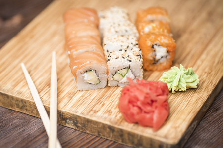 Set of sushi rolls with salmon, sesame, red caviar, avocado, Philadelphia cheese, cucumber, ginger, wasabi and sushi sticks on a light wooden board Stock Photo