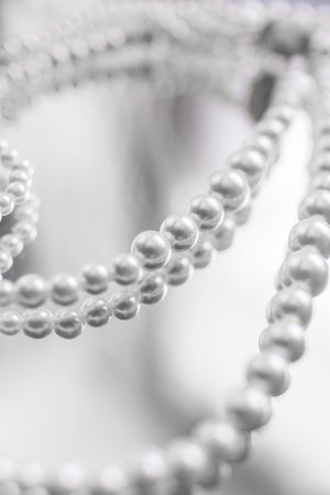 A necklace of white pearls lies on a light washed out mirror background