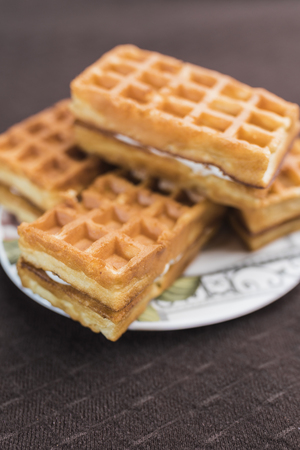 Sweet Viennese waffles with white filling lie on a saucer on a dark brown background, vertical frame Stock Photo