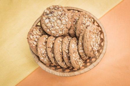 Homemade cookies with cereals and seeds in a wicker basket on a pear-yellow and light orange warm background, top view