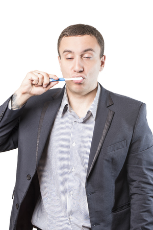 Sleepy man in a suit cleans his teeth with closed eyes, isolated on a white background