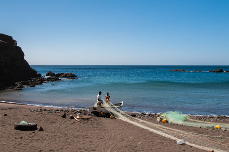 santiago cape verde: Fishermen mending their nets for the next fishing on a beach in Santiago, Cape Verde