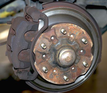 Image of rusted brake caliper, worn brake pad and grooved brake rotor. Repair needed. Stock Photo
