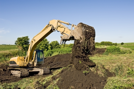 Excavator moving dirt in farmers field to build low water crossing  Stok Fotoğraf
