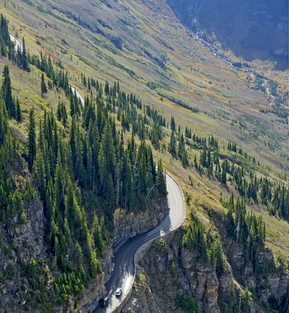 Glacier National Park: Going-to-the-Sun-Road Viewed from the Highline Trail, Glacier National Park, Montana.  All trademarks or elements protected by industrial or intellectual property laws have been removed from the two autos. Stock Photo