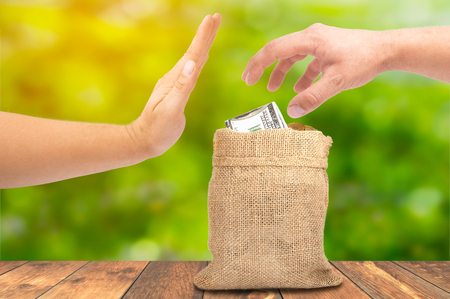 A theft money concept, A hand theft money from sack bag with dollar sign, corruption concept Stock Photo
